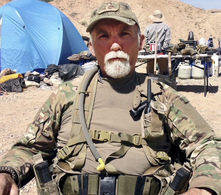 """Gerald """"Jerry"""" DeLemus of Rochester, N.H., sits among a group of militia members camping on Cliven Bundy's ranch near Bunkerville, Nev., in 2014.(photo the Associated Press)"""